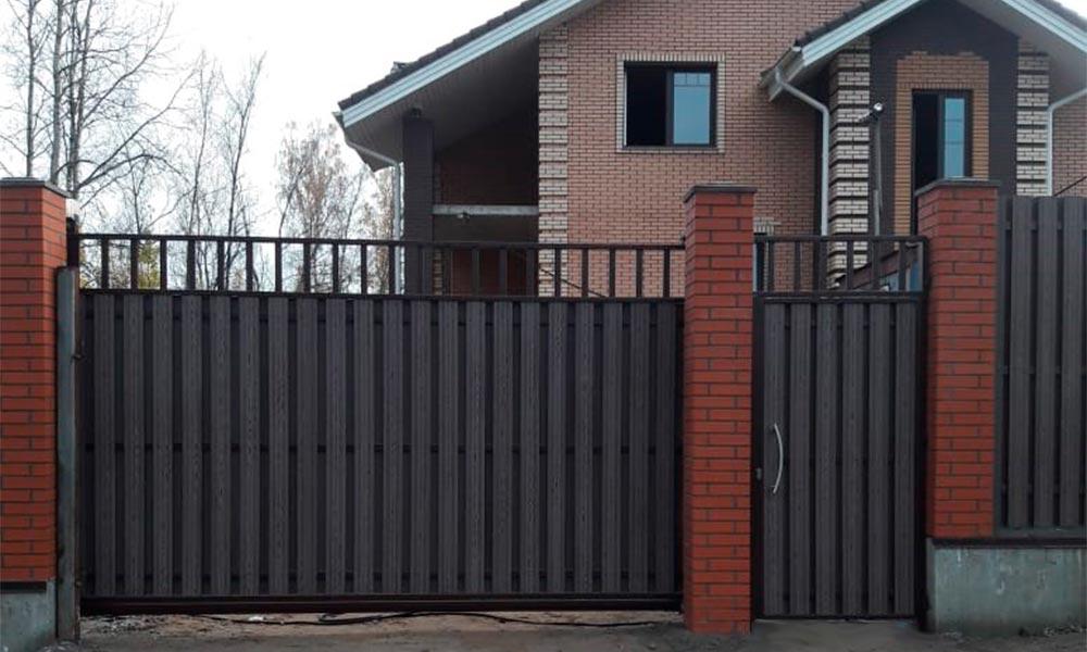 Откатные ворота, зашитые композитной доской с решеткой сверху. Отдельно стоящая калитка в стиле ворот.